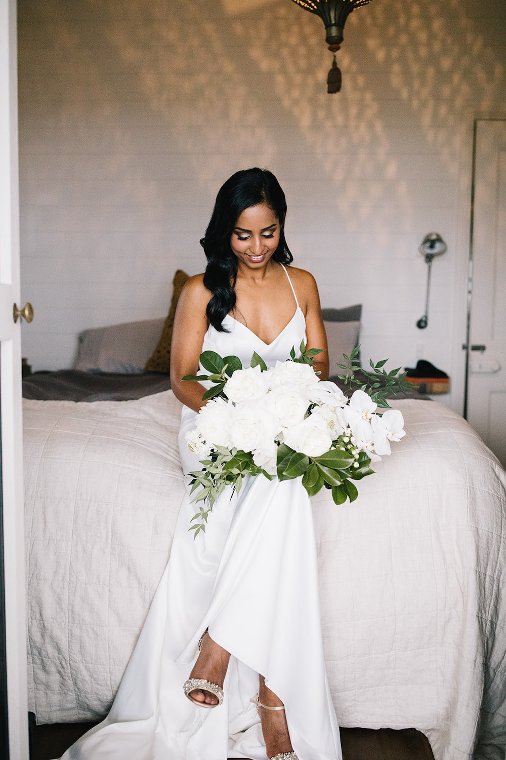 Bride sitting on bed with flower bouquet / Byron Bay