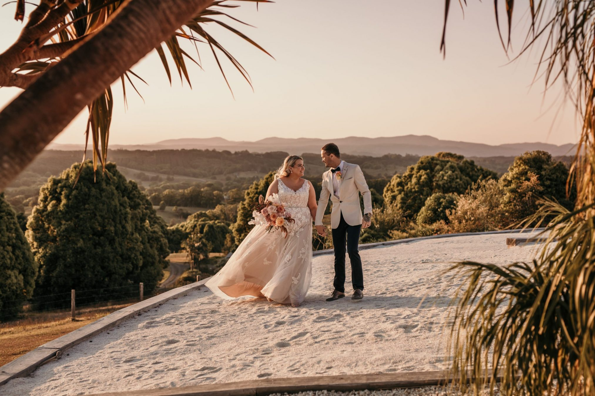 Bride and groom hold hands at sunset at temple farmhouse.