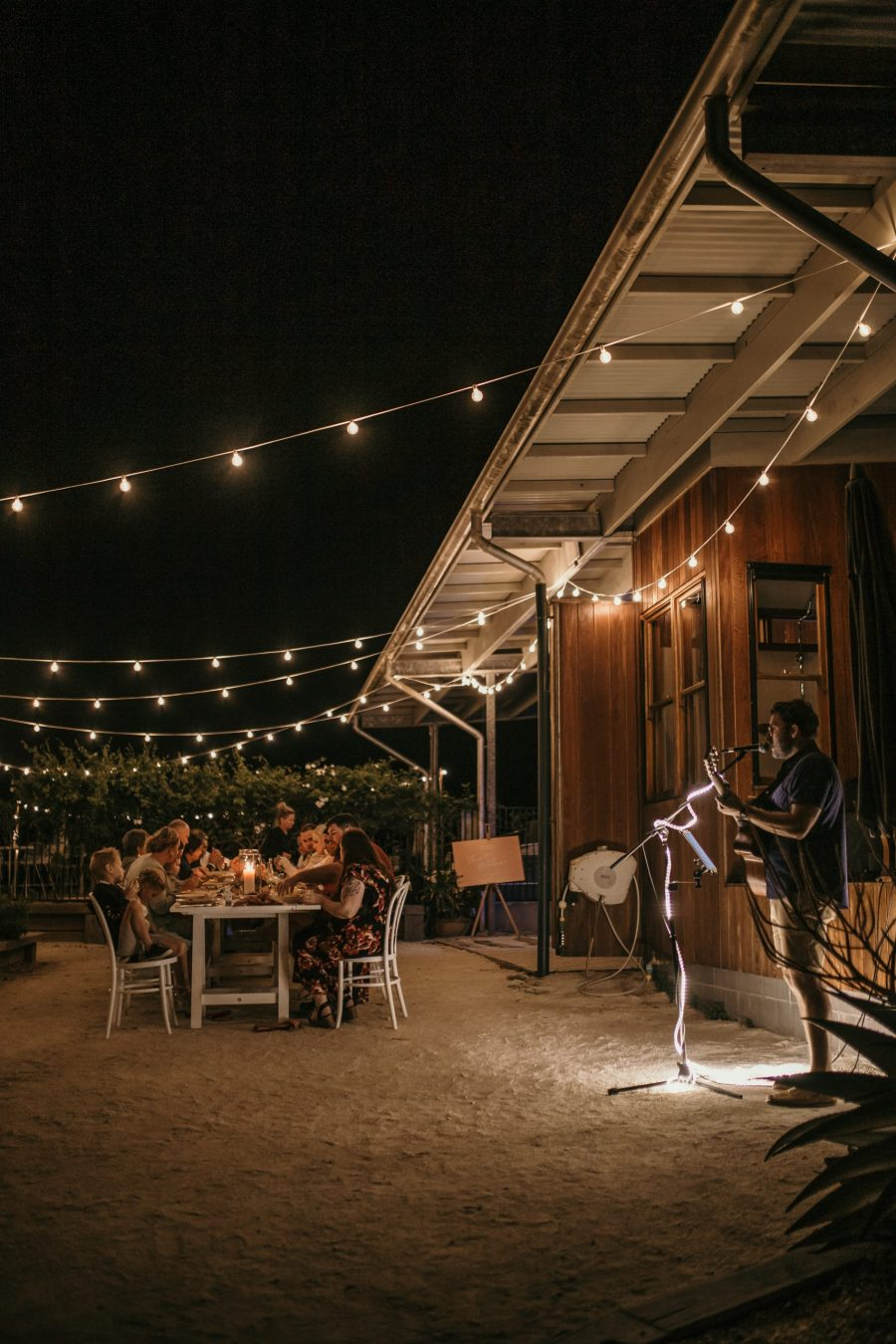 Guests enjoy dinner while musician plays guitar.