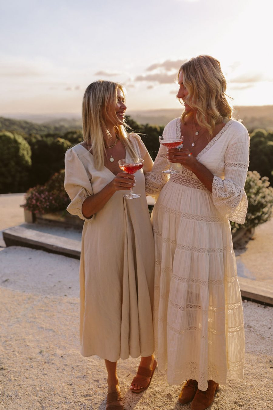 Ladies cheers with cocktail with sunset in background.