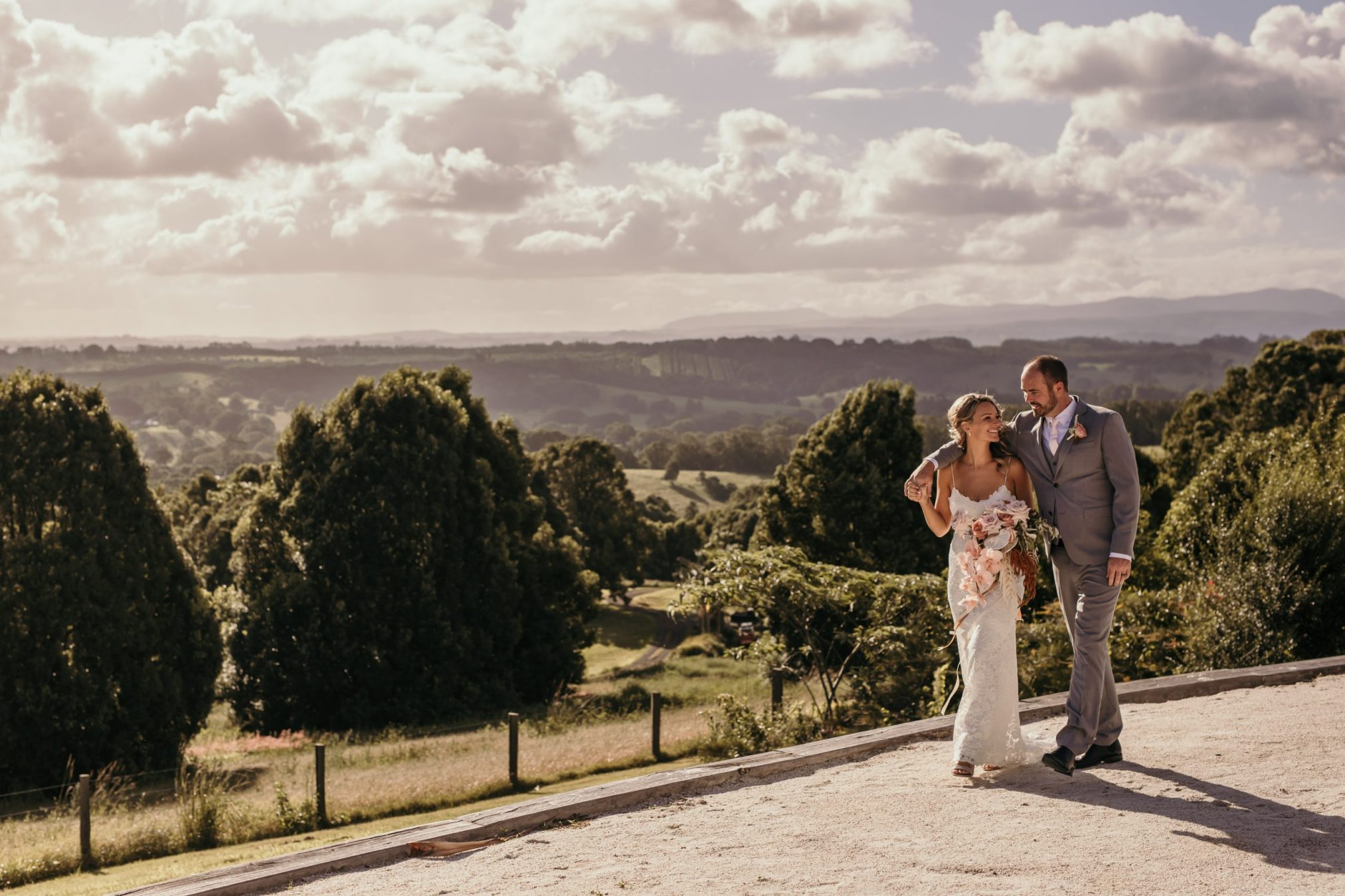 Bride and groom smile as they walk at Temple Farmhouse. Views to hillside in background.