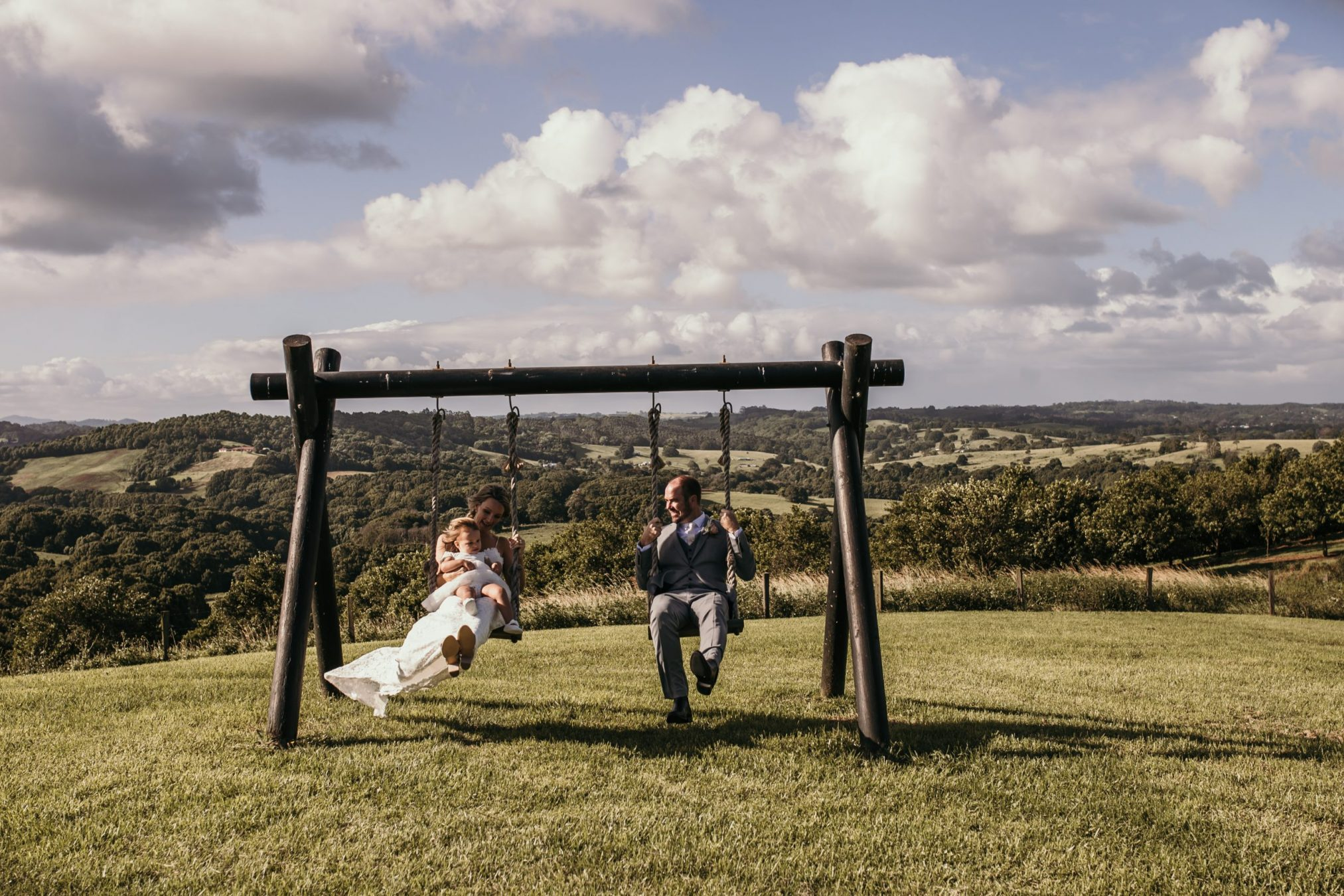 Bride and groom on swing with child on brides lap. View to valley in background.
