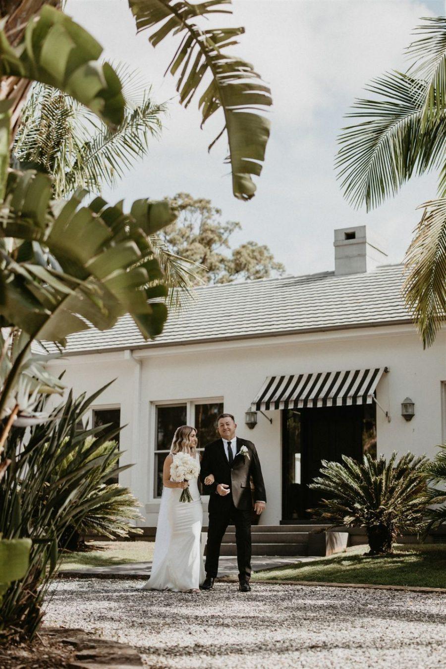Bride and dad walk along side wedding venue.