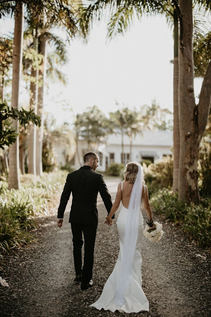 Bride and groom hold hands while walking down drive way to wedding location.