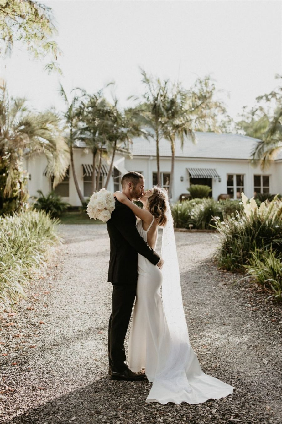 Bride and groom kiss with flower bouquet in hand.