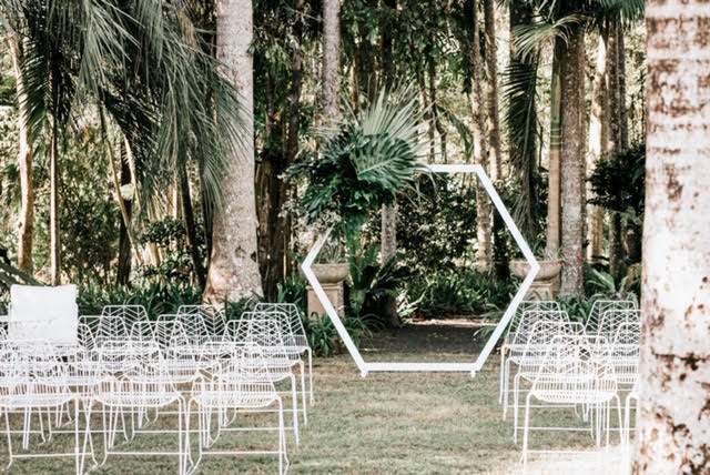 White alter with flowers and white chairs ready for guests.