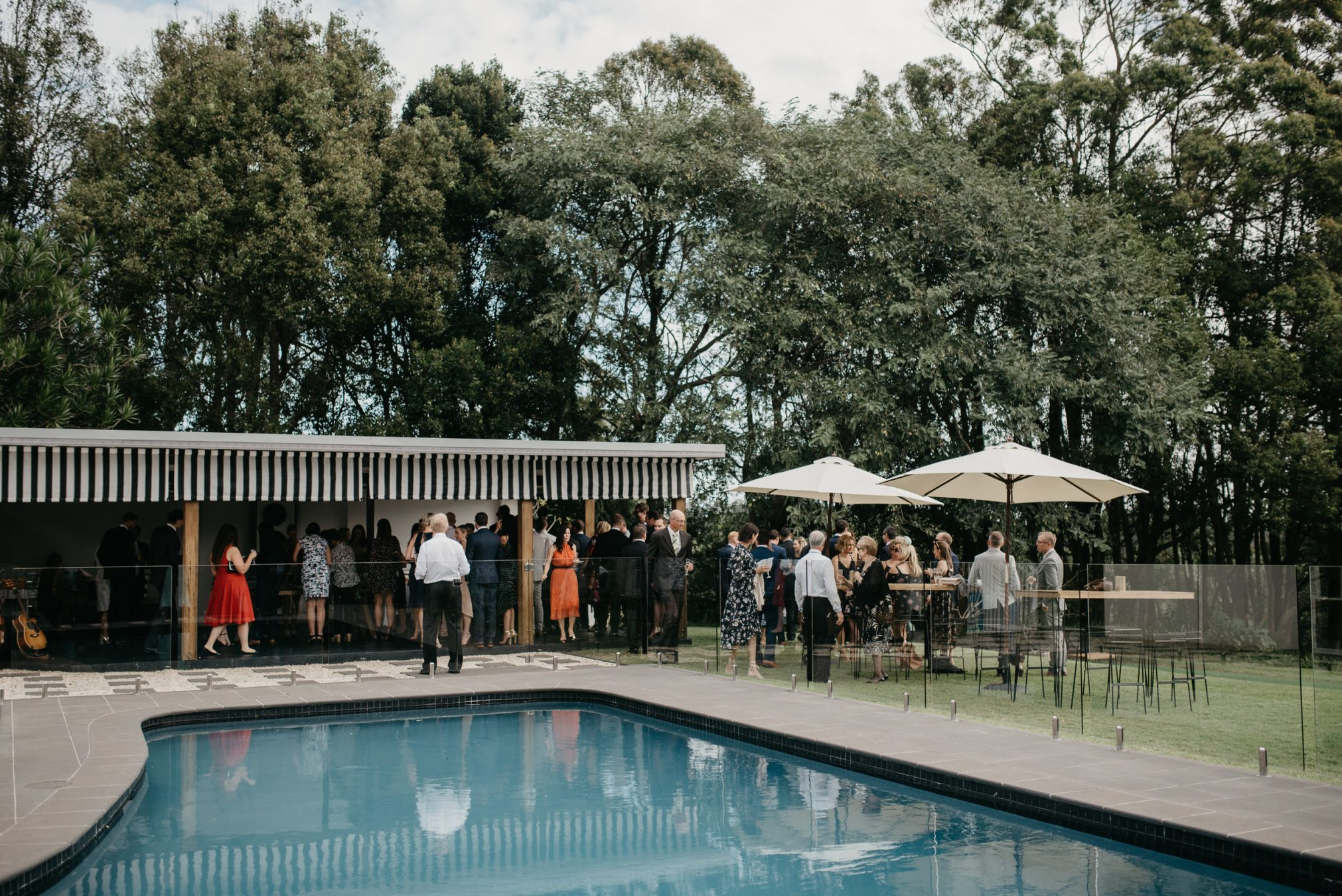 Wedding guests enjoying their time outside by the pool.