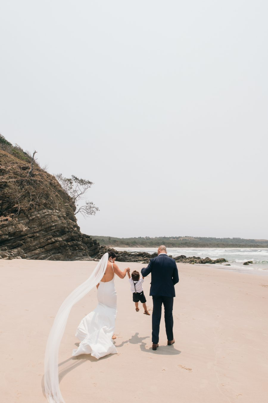 Bride and groom walk down beach with child / Broken Head Byron