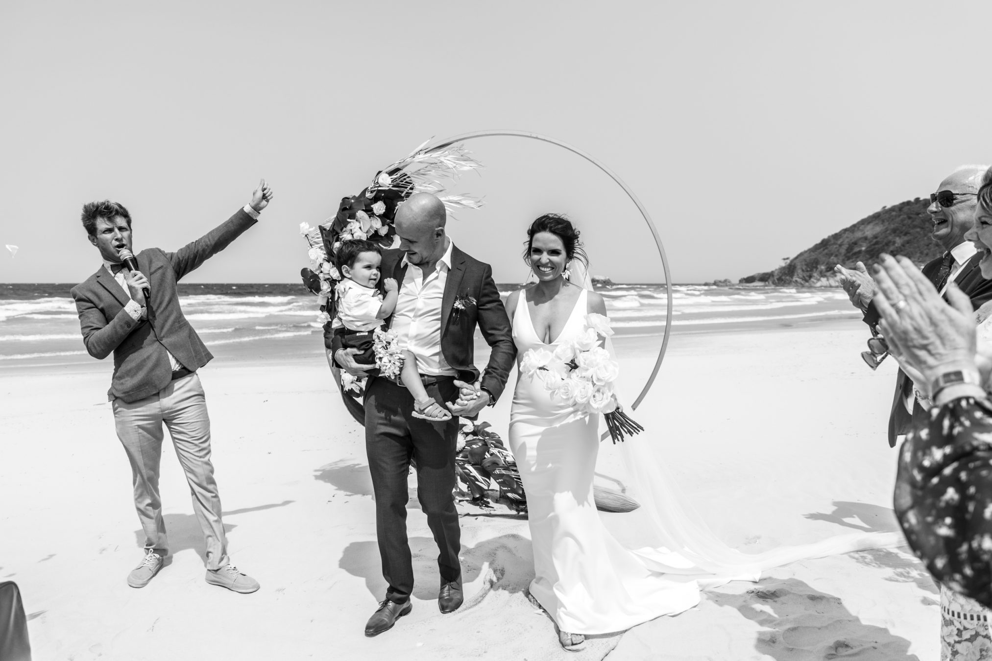 Bride and groom walking down beach with child. Audience claps. Broken Head Byron