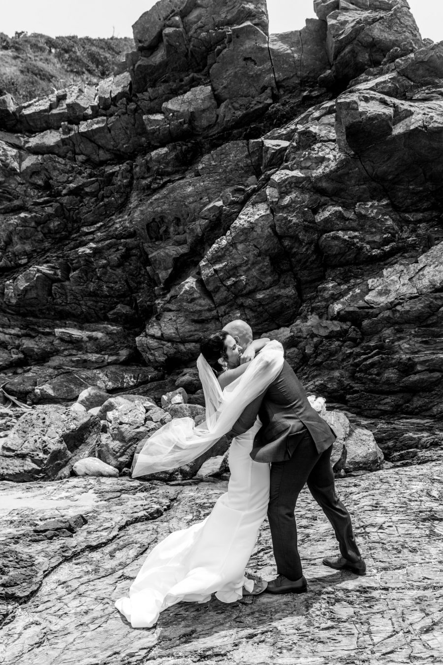 Bride and groom hugging amongst rocks in Broken Head Byron