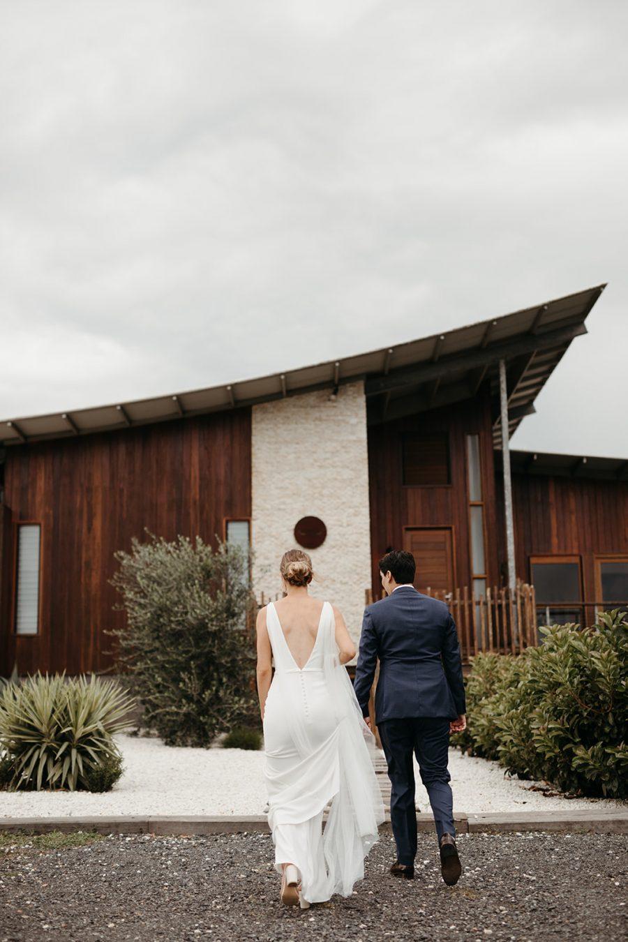 Bride and groom walk towards wedding venue (temple farmhouse)