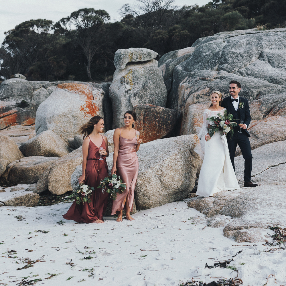 Bridal party relax in classic beach wedding with style in Tasmania.