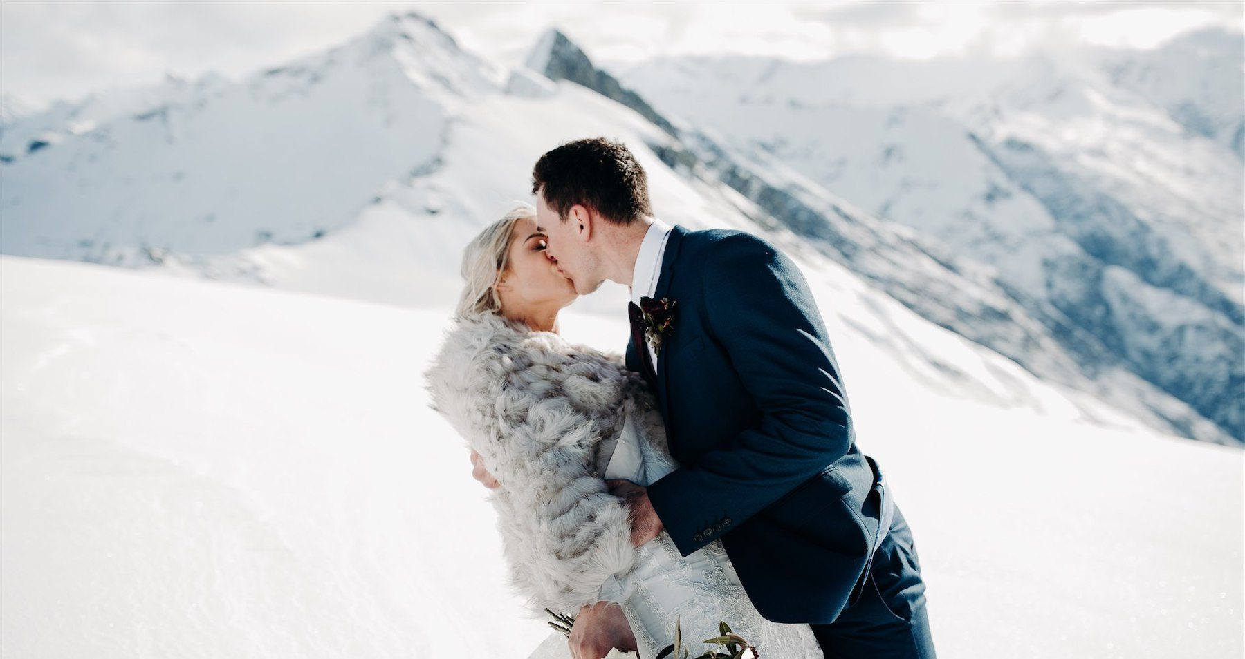 Bride and groom kiss in snow- New Zealand