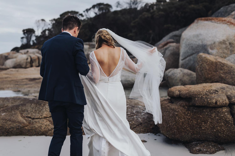 Bride and groom walk on beach at Bay of Fires wedding in Tasmania