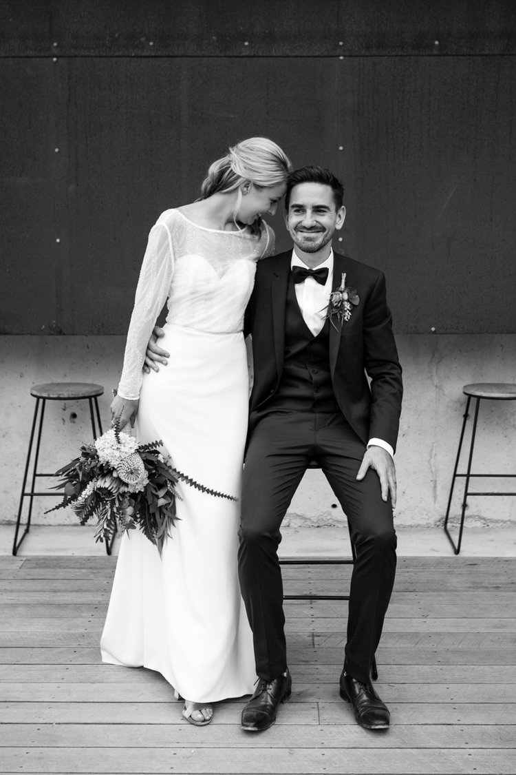 bride and groom smile with groom sitting and bride standing in stylish wedding at bay of fires bush retreat