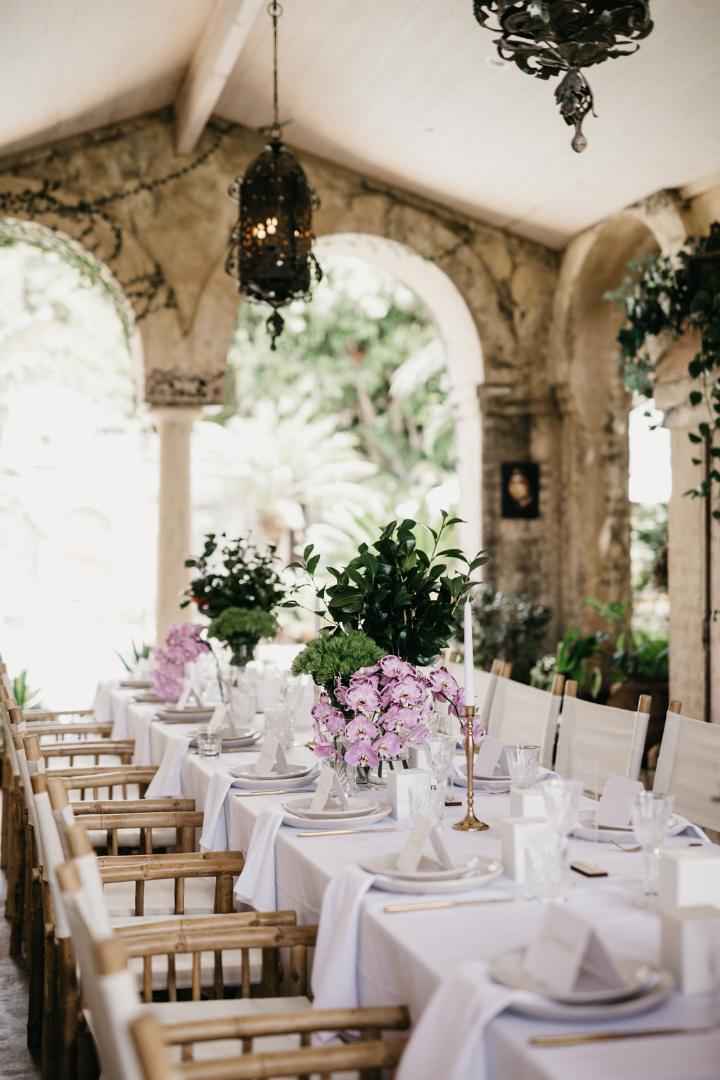 Reception table set up with flowers in rustic building / wedding photography