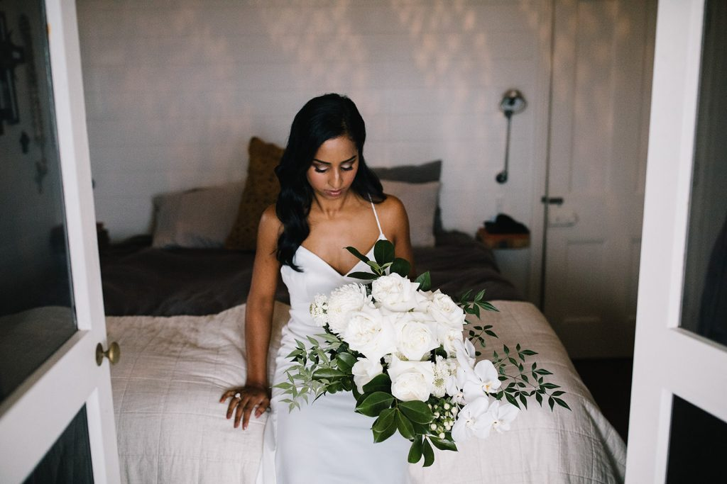 Bride sitting on bed with flower bouquet / Wedding photography