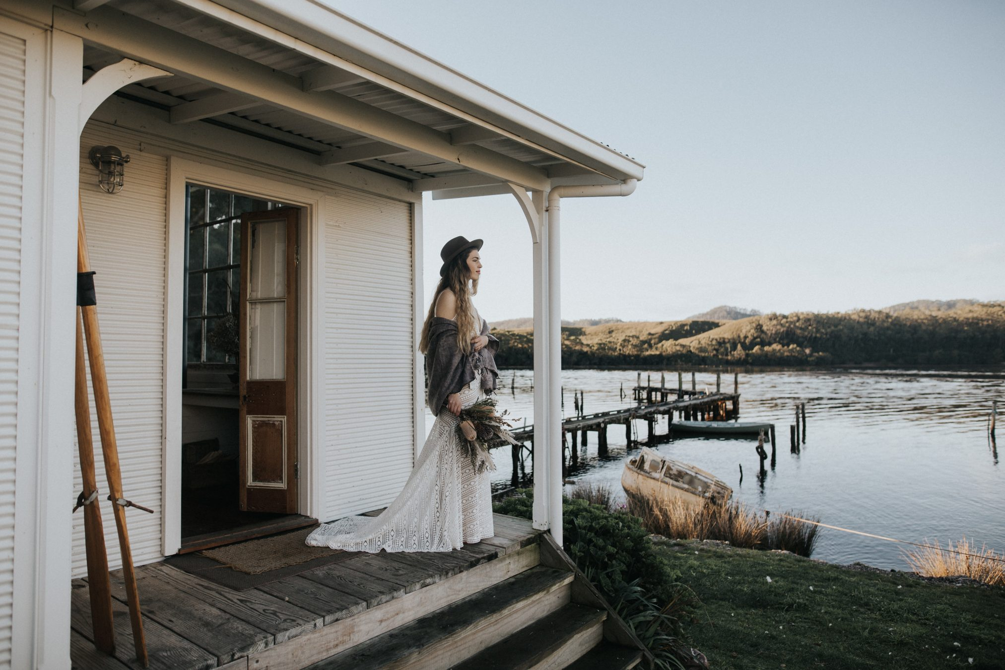 Bride standing by water outside of rustic house - Captains Rest Tasmania
