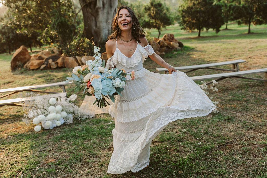 Bride holing bouquet laughing / Byron Bath House Wedding