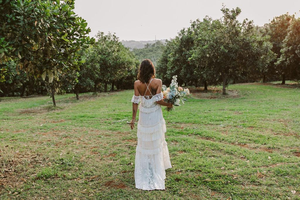 Bride holing bouquet in lush greenery / Byron Bath House Wedding
