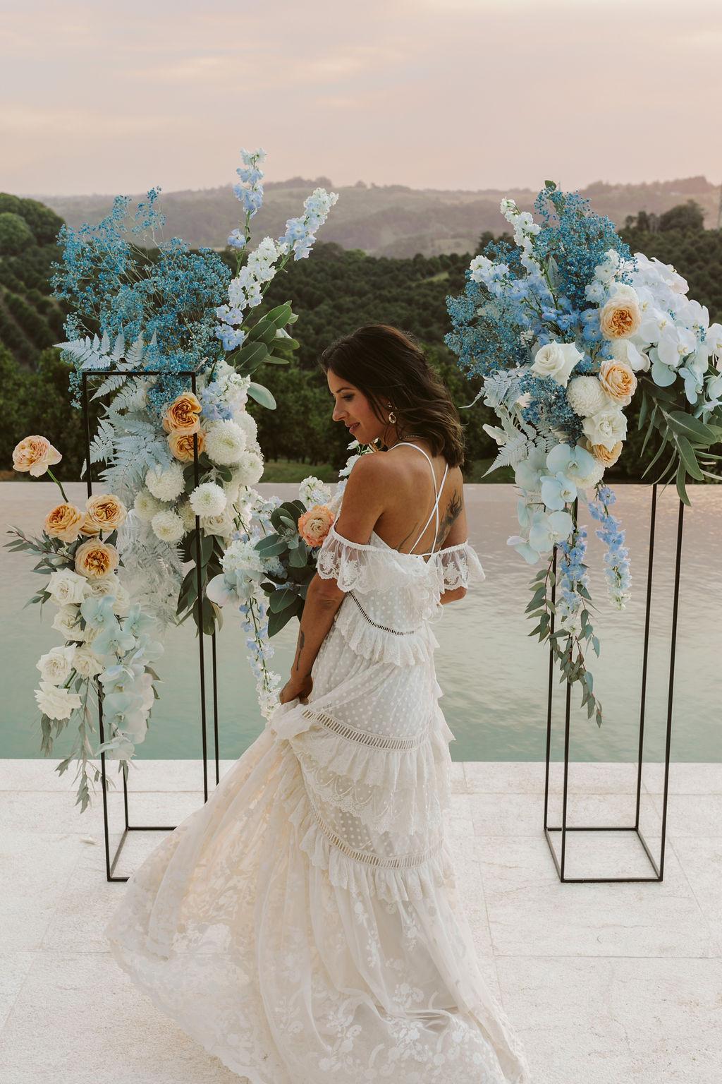 Bride standing at flower arrangement at sunset / Byron Bath House Wedding