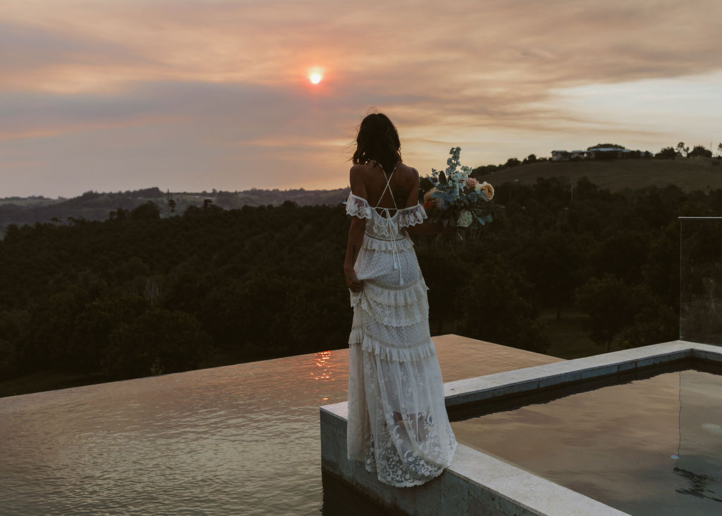 Bride standing at sunset / Byron Bay Bath House