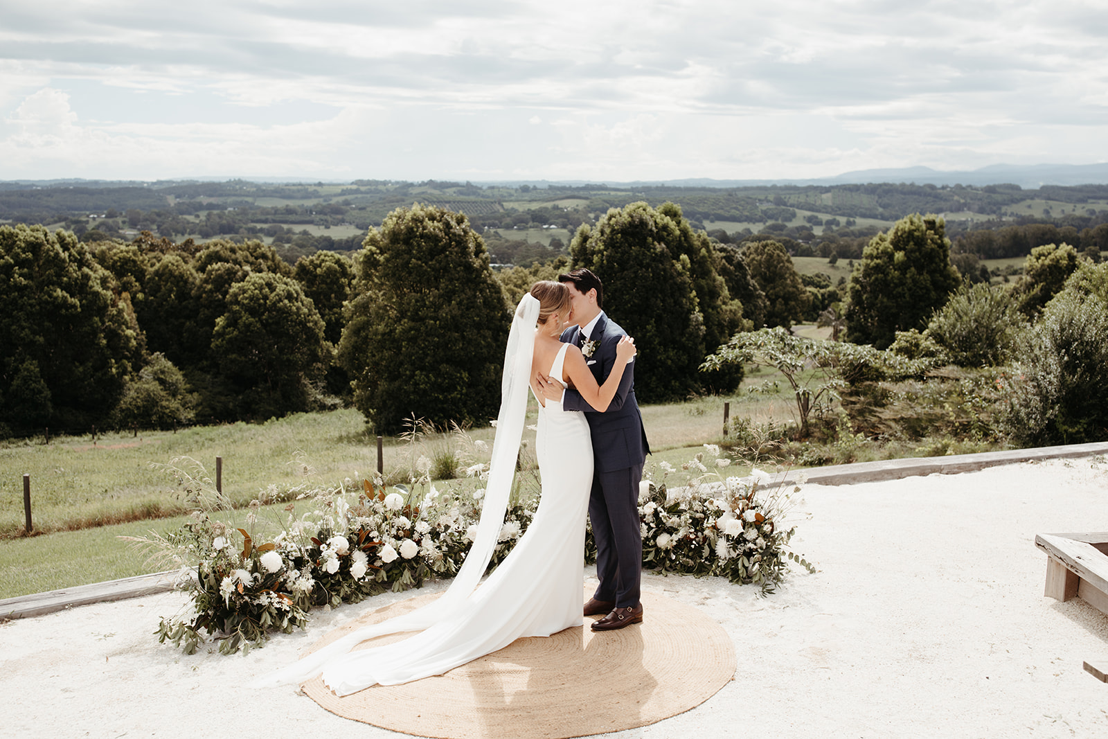 Bride and groom kiss by flowers / Temple Farmhouse / Micro Wedding