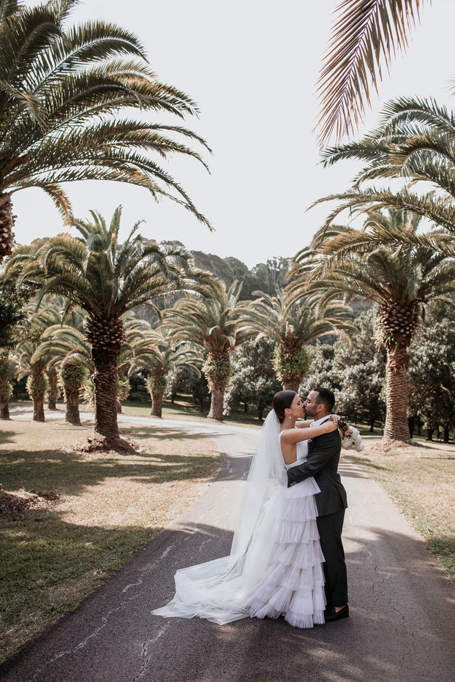Bride and groom kiss in front of driveway with palm trees.