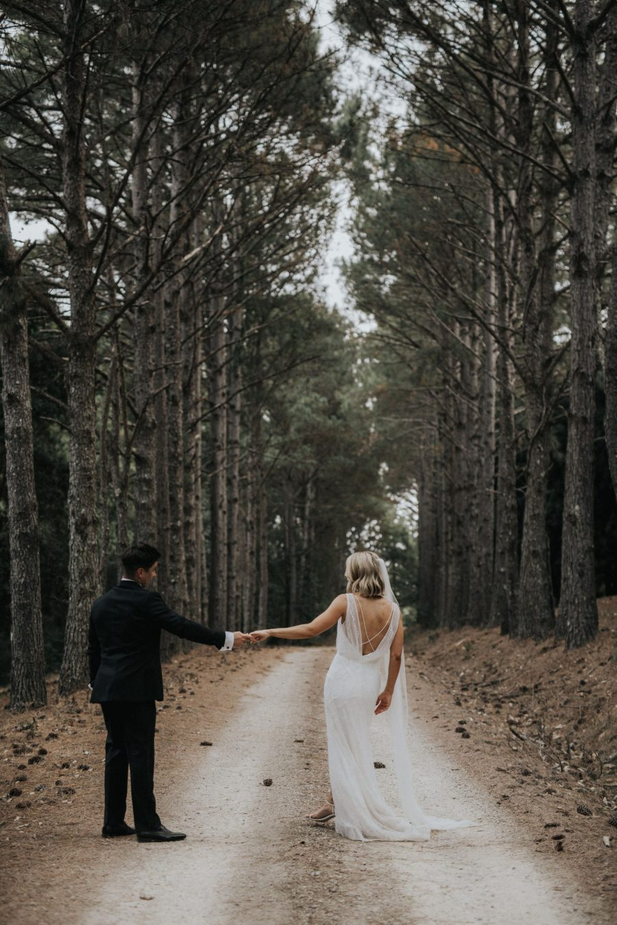 Bride and groom hold hands as they walk through Byron trees.