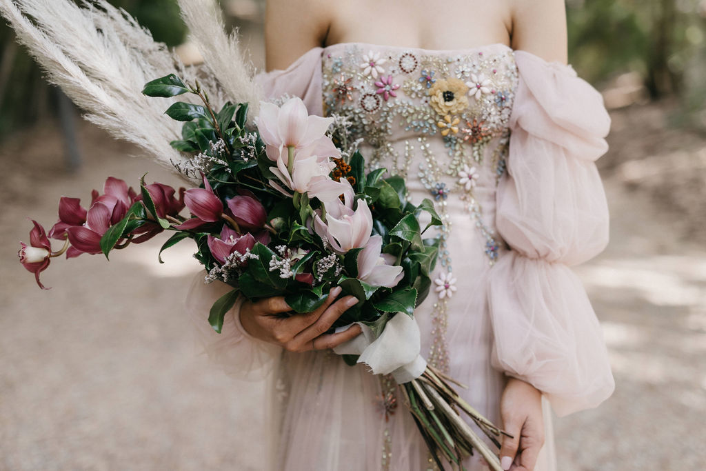 Close up of the brides flower bouquet and off the shoulder wedding dress with embellishments.