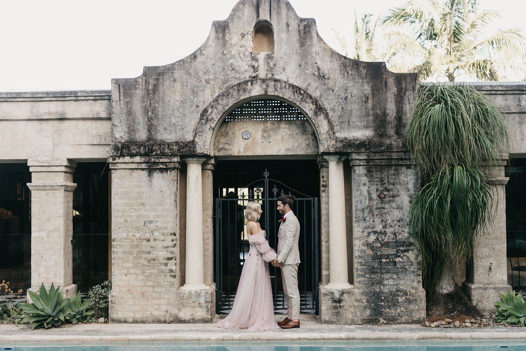 Bride and groom hold hands and look at each other in front of rustic villa and pool.