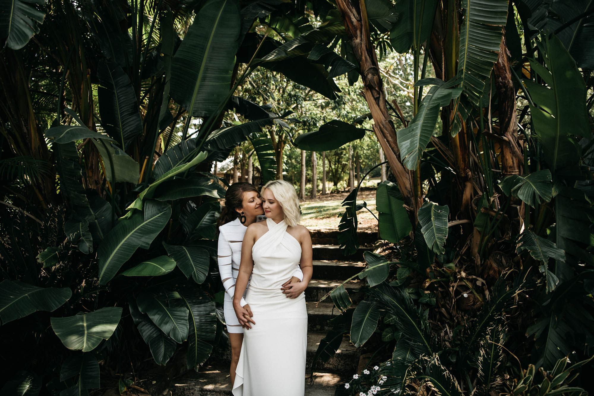 Two ladies both in white standing amongst green palms.