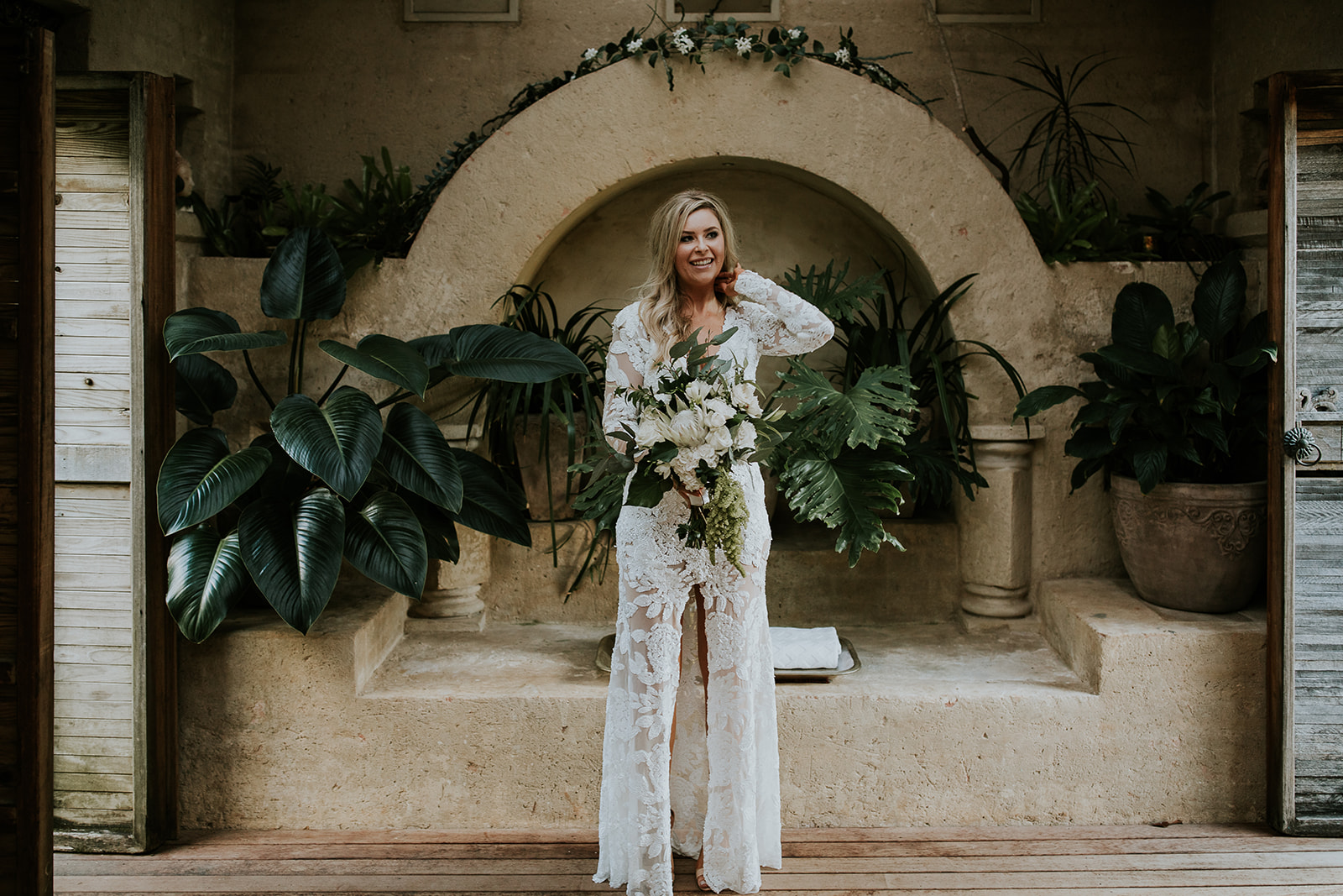 Bride standing in front of rustic alter with a bouquet of flowers.