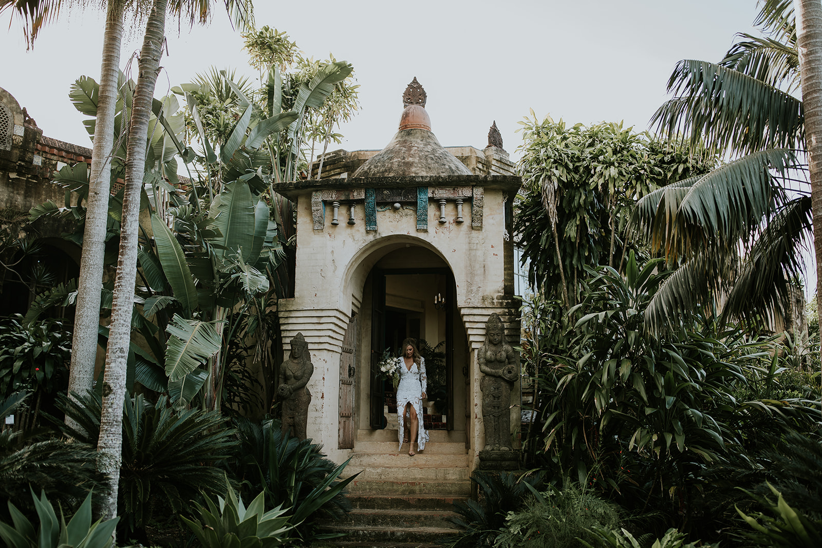 Bride walking down stairs of rustic villa. Green jungle surrounds building.