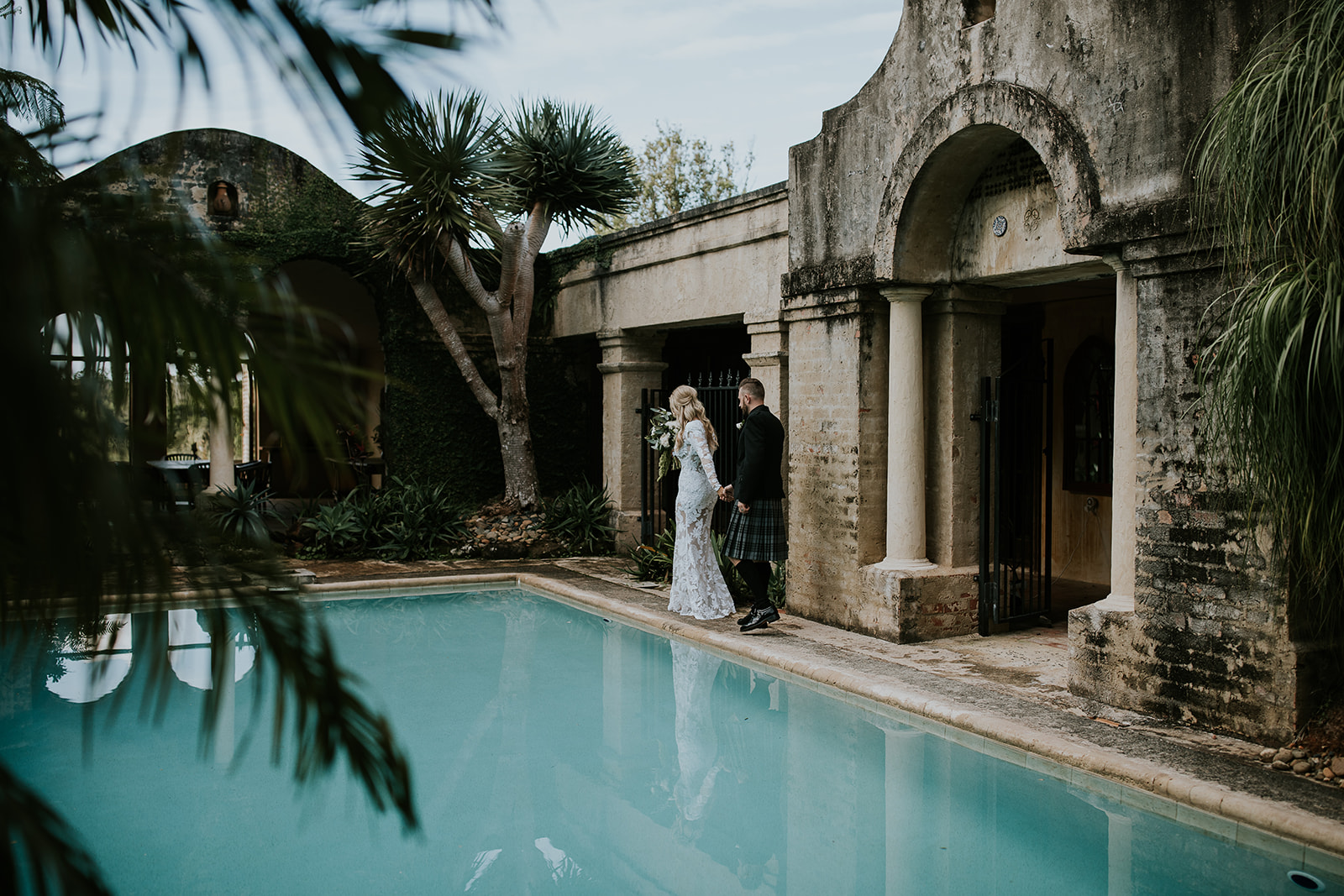 Bride leading groom around rustic pool villa.