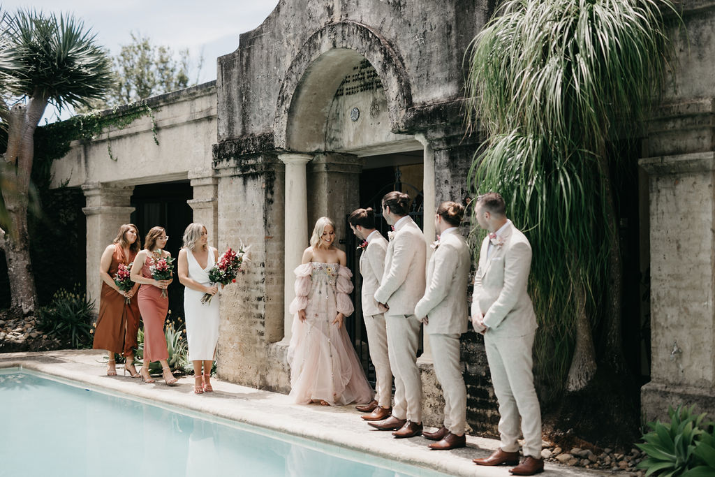 Bride and groom wedding party standing by the pool in rustic villa.