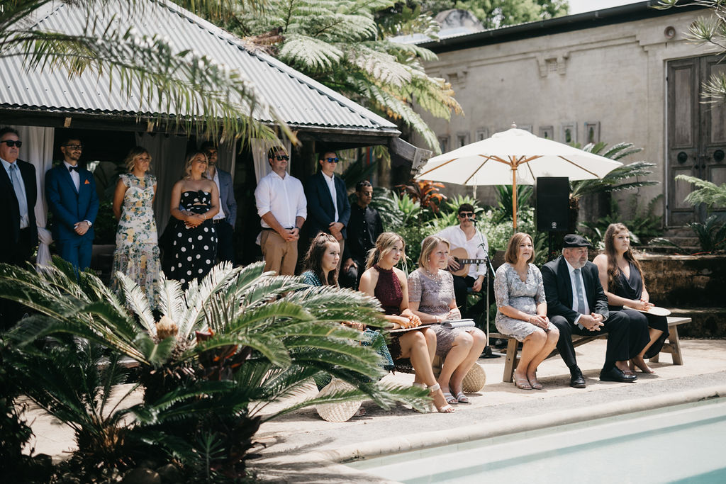 Friends and family sit by the pool looking at bride and groom.