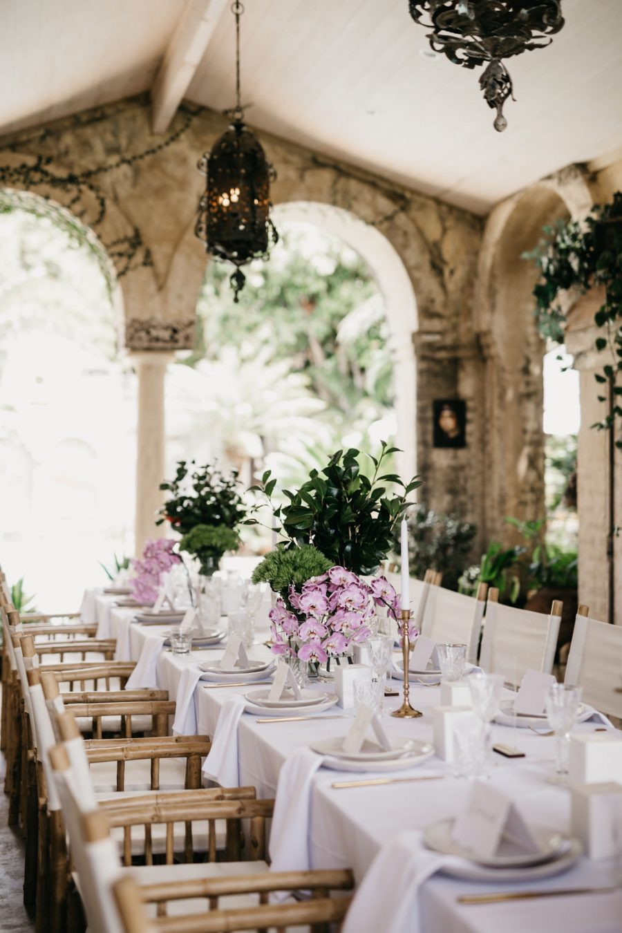 Wedding reception set up in rustic villa. Soft purple flowers and cane chairs.