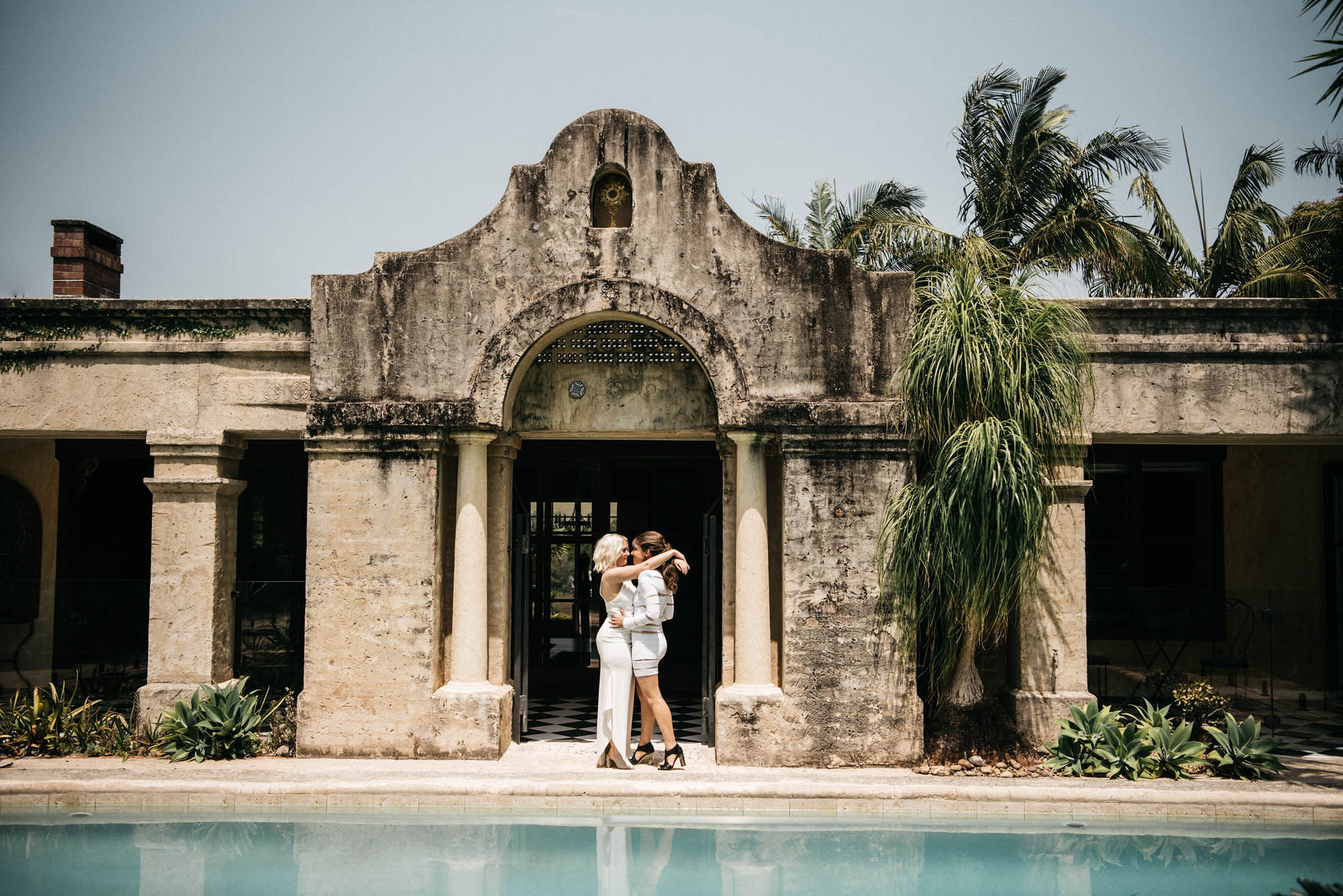 Couple holding each other with rustic concrete villa and blue pool in background.